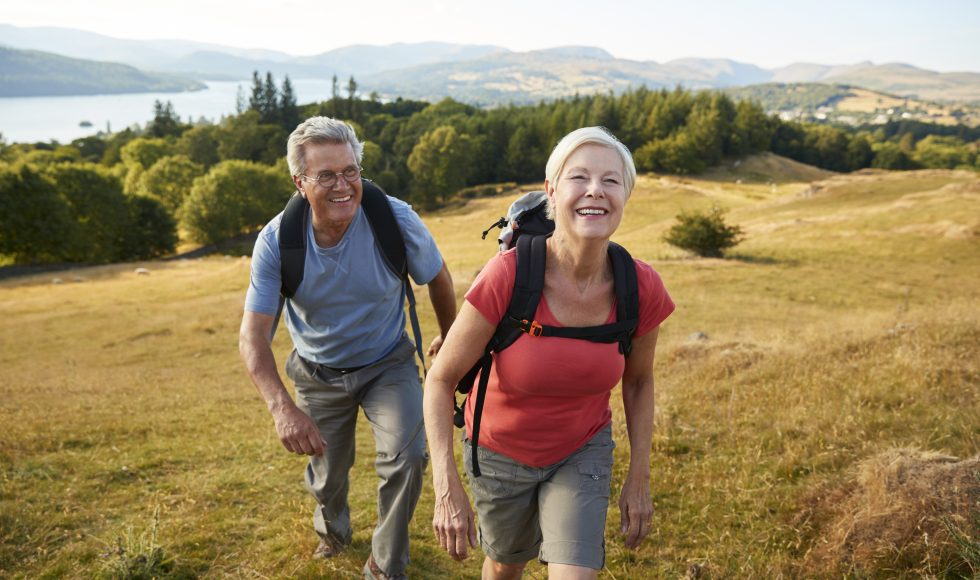 Senior Couple Climbing Hill On Hike Through Countryside Together